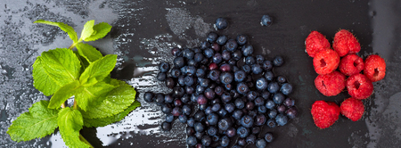 luscious: Fresh washed raspberries, blueberries, mint leaves with waterdrops. Organic berries on grey slate stone board. Smoothie ingredients. Banner for website.