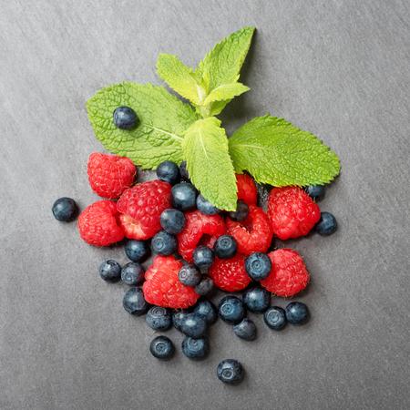 luscious: Fresh washed raspberries, blueberries and mint leaves. Organic berries on grey slate stone board. Top view.