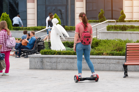 Young woman riding a hoverboard on the city square. New movement and transport technologies. Dual wheel self balancing electric skateboard. People on electrical scooter outdoors. Stock Photo