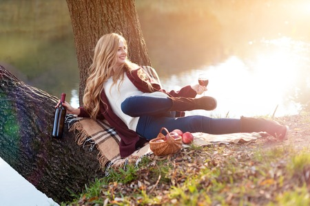Beautiful woman drinking wine outdoors having picnic in the park. Portrait of young blonde beauty enjoying a glass of red wine sittind on autumn lawn near the lake.