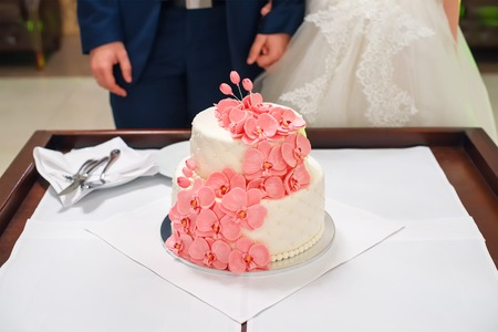 Bride and groom cutting their wedding cake decorated with orchids.