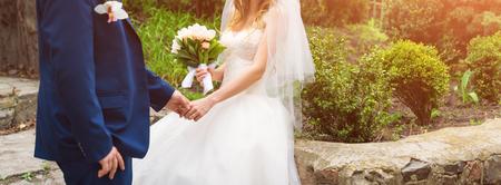 結婚式当日の新郎新婦エレガントな結婚式のカップルが庭でロマンチックな瞬間を楽しむ結婚式の日に屋外で一緒にポーズします。Web サイトのバナ