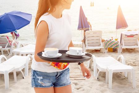 소녀 웨이터 해변에서 커피를 들고입니다. 음료를 제공하는 여자. 바다와 해변 sunbeds 배경에. 바다에서 여름 휴가입니다. 스톡 콘텐츠