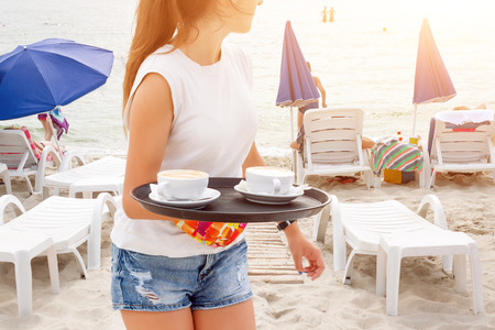 Girl waiter carrying coffee on the beach. Woman serving drinks. Sea and beach sunbeds on the background. Summer vacation at the sea. Archivio Fotografico