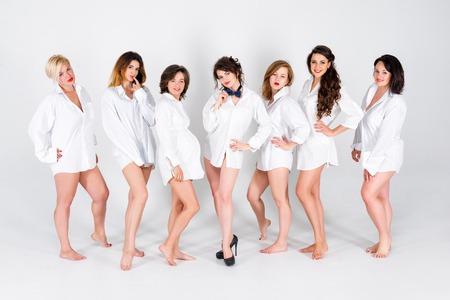 Elegante damigelle d'onore divertirsi con la sposa indossando camicie bianche. Le allegre felici ragazze festeggiano una festa di nubilato di sposa. Sparare da studio.