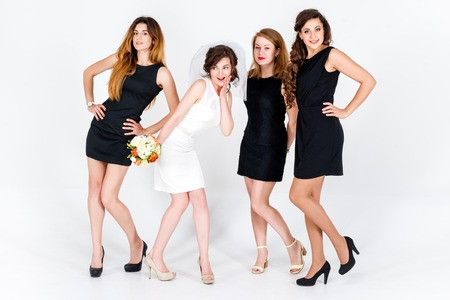 Stylish bridesmaids having fun with bride. Cheerful happy girls celebrate a bachelorette party of bride. Studio shoot. Zdjęcie Seryjne