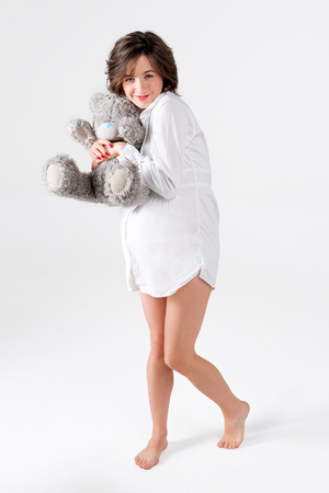 Pregnant woman holding soft toy. Pretty young woman carrying teddy bear.
