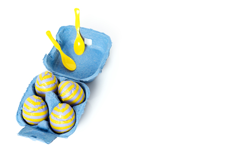 Foil covered chocolate easter eggs with plastic spoons in paper box on white background. Free copyspace for text. Stock Photo