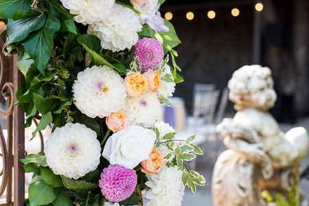 Wedding arch with flowers outdoors. Beautiful wedding set up. Wedding ceremony in the garden with sculptures and fountain. Part of the festive decor, floral arrangement.