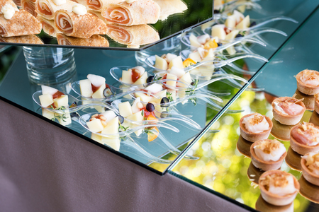 Appetizers, finger food, party food, sliders. Canape, tapas. Served table at summer terrace cafe. Catering service. Outdoor restaurant table with food. Stock Photo