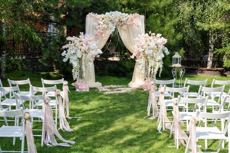 Huwelijksboog die met doek en bloemen in openlucht wordt verfraaid. Mooie bruiloftsopstelling. Huwelijksceremonie op groen gazon in de tuin. Onderdeel van het feestelijke decor, bloemstuk.