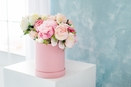 Flowers in round luxury present box. Bouquet of pink and white peonies in paper box near the window.Mock-up of hat box of flowers with free copyspace for text. Interior decoration in in pastel colors.