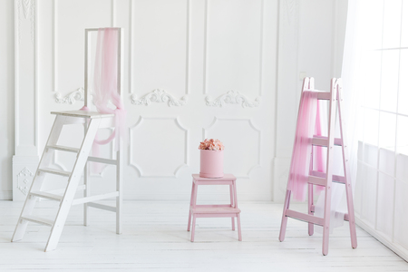 babyroom: Simple white interior, pink ladder decor and flowers in the box.