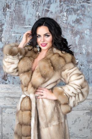 Brunette woman with jewelry wearing luxury fur coat. Fashion model girl portrait, studio shot. Winter clothes.