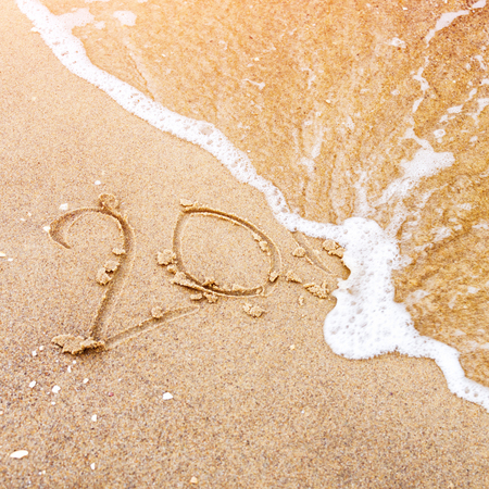 New Year is coming concept - inscription 20 on a beach sand, sea wave is covering digits 2017 or 2018. New Year celebration on tropical island, tourism, travel tour.