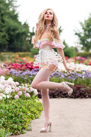 Sexy blonde woman wearing beautiful lingerie with stockings and corset, walking in blooming garden. Hot female in underware posing in sensual way outdoors. Female fashion, model fitted like a doll, barbie.