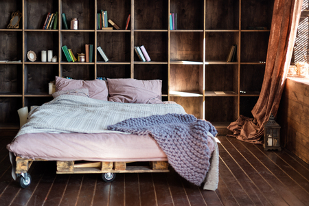 Modern bedroom in a loft. Urban apartment with pallet bed, scandinavian eco design. 免版税图像