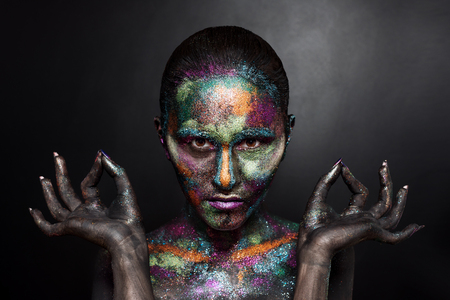 bodypainting: Young artistic woman in black paint and colourful powder. Glowing dark makeup. Creative body art on the theme of space and stars. Bodypainting project: art, beauty, fashion.
