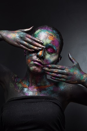 Mujer artística joven en pintura negra y polvo colorido. Maquillaje oscuro que brilla intensamente. Arte corporal creativo sobre el tema del espacio y las estrellas. Proyecto de Bodypainting: arte, belleza, moda.