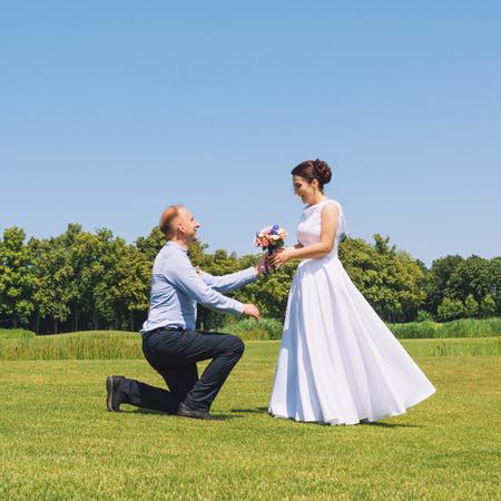 男は、結婚する彼のガール フレンドを提案。結婚の提案。愛と結婚の概念。公園で若い魅力的な陽気なカップル。 写真素材