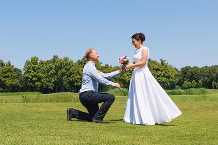 Man makes a proposal to his girlfriend to get married. Marriage proposal. Love and marriage concept. Young attractive cheerful couple in the park.