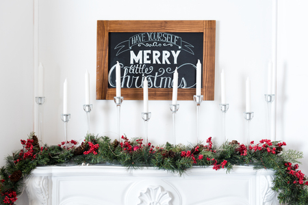 fireplace: Beautiful Christmas interior. New year decoration. Comfort home. Candles in a metal candlestick on the fireplace.