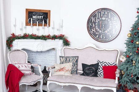 fireplace: Beautiful Christmas interior. New year decoration. Comfort home. Classic new year tree decorated in a room with fireplace.