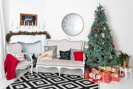 Beautiful Christmas interior. New year decoration. Comfort home. Classic new year tree decorated in a room with fireplace.