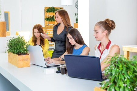 Group of pretty businesswoman working together with new startup project using laptop computer in modern loft. People and teamwork concept - happy creative team in office. Women in businness.