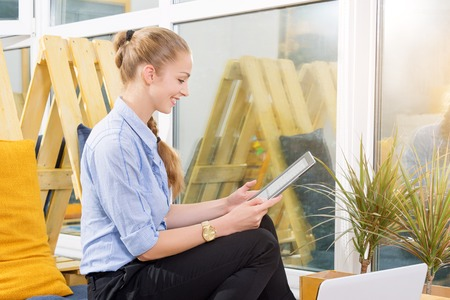 Pretty businesswoman working with new startup project using tablet in modern loft. Woman in businness. Stock Photo