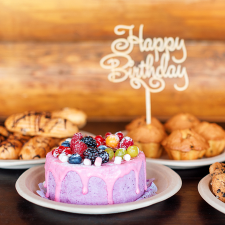 Birthday cake and muffins with wooden greeting sign on rustic background. Wooden sing with letters Happy Birthday and holiday sweets.