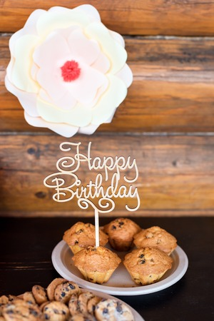 birthday cakes and muffins with wooden greeting sign on rustic background wooden sing with letters