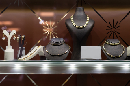 Variety of jewelry in store window. Rings, bracelets, earrings and necklaces on stands for sale Stock Photo