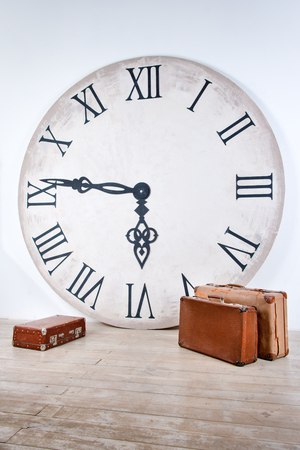 Vintage classic brown leather suitcases and big clock. World time in interior concept. Vacation travel holiday background Stock Photo