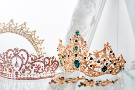 Royal luxury gold and silver crowns decorated with precious stones. Diamond tiaras with gemstones for prom and wedding. Selective focus