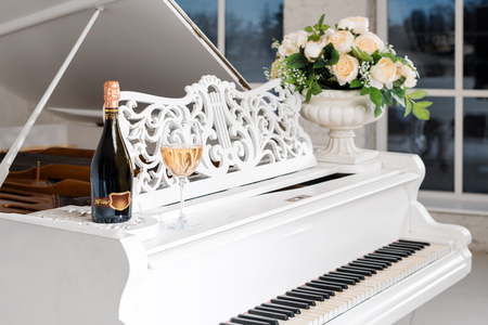 Grand piano in a luxury white classic interior with wine, palms and flowers. Banque d'images
