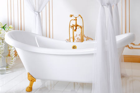 Luxury bathroom in light colors with golden furniture details and canopy. Elegant classic interior Stock Photo