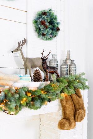 Mantelpiece with Christmas decorations. Cozy winter scene. White interior details with lights