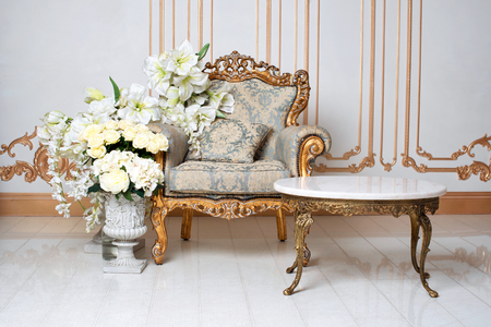 Luksusowe wnętrze vintage w arystokratycznym stylu z eleganckim fotelem i kwiatami. Retro, klasyka