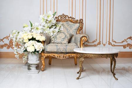 Luxuriöses Vintage-Interieur im aristokratischen Stil mit elegantem Sessel und Blumen. Retro, Klassiker