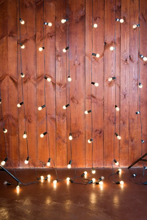 Light bulbs on wooden background. Vintage edison light bulbs garland in loft interior