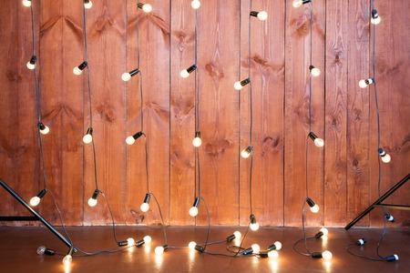 Light bulbs on wooden background. Vintage edison light bulbs garland in loft interior.
