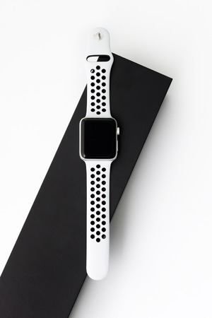 Modern technology, time, object and media concept - close up of sport smart watch on white background with dark watch box