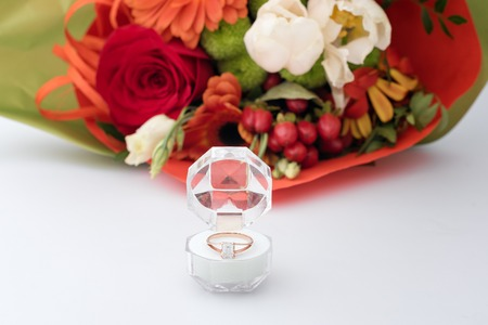 Engagement ring in a gift box with bright bouquet of flowers. The offer to get married. Gift for St. Valentine's Day. Marriage proposal for beloved woman. Symbol of love and marriage Foto de archivo