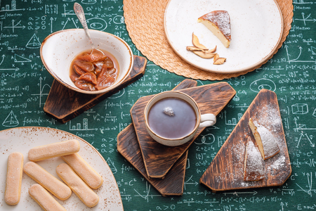 Tea time. Apricot jam, cottage cheese pie and cup of tea on wooden boards. Mathematical formulas on tablecloth background Stock fotó