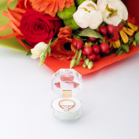 Engagement ring in a gift box with bright bouquet of flowers. The offer to get married. Gift for St. Valentines Day. Marriage proposal for beloved woman. Symbol of love and marriage.