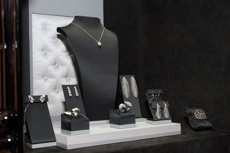 Variety of jewelry in store window. Rings, bracelets, earrings and necklaces on stands for sale.