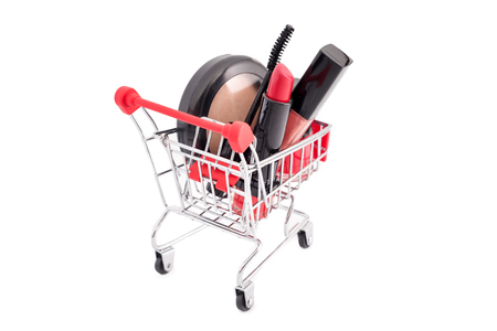 Makeup in pushcart isolated on white background. Red lipstick, mascara, pink lip gloss, powder, nail polish. Makeup products in shopping cart, discount or sale theme. Must haves and beauty favorites