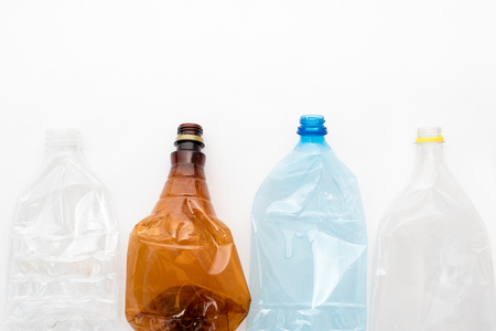 Different types of crushed plastic bottles on white background. Copyspace for text. Recyclable waste. Recycling, reuse, garbage disposal, resources, environment and ecology concept