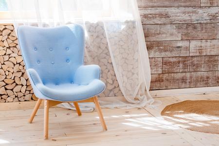 Comfortabele zachte fauteuil in scandinavisch eco loft appartement. Moderne minimalistische woonkamer met houtstapel Stockfoto